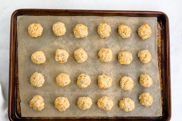 a baking sheet with 24 sausage balls