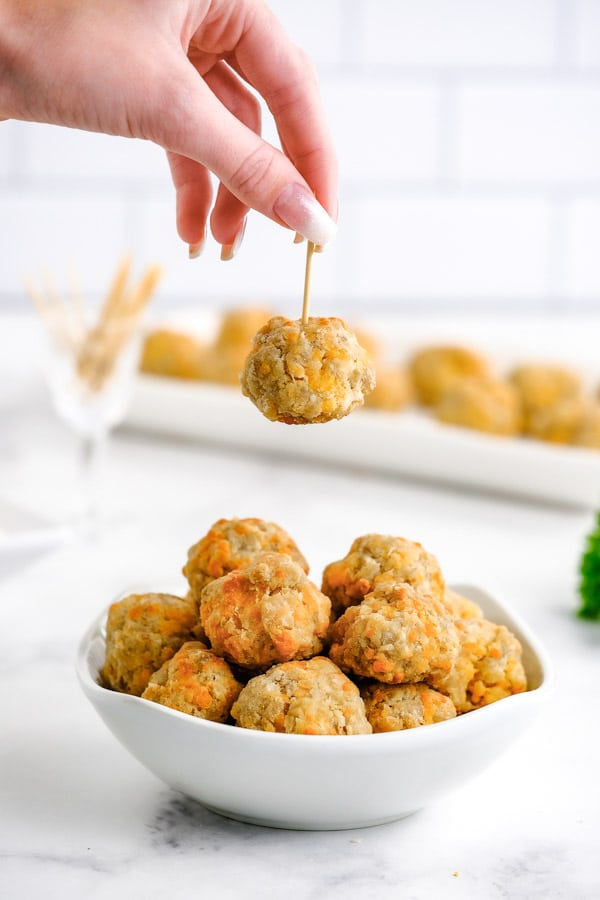 a ladies hand holding a sausage balls by a toothpick over a bowl of sausage balls