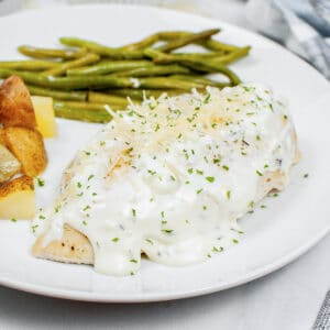 closeup of herb chicken covered with creamy sauce on a plate with potatoes and green beans
