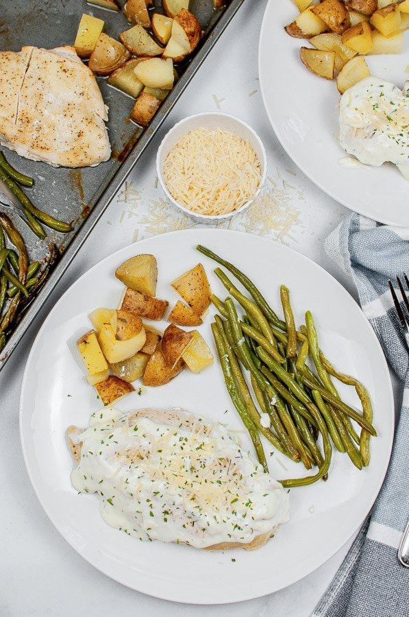 a white plate with creamy chicken, died potatoes and green beans