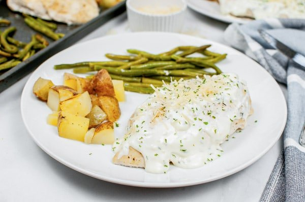 a white plate with creamy sheet pan chicken potatoes and green beans