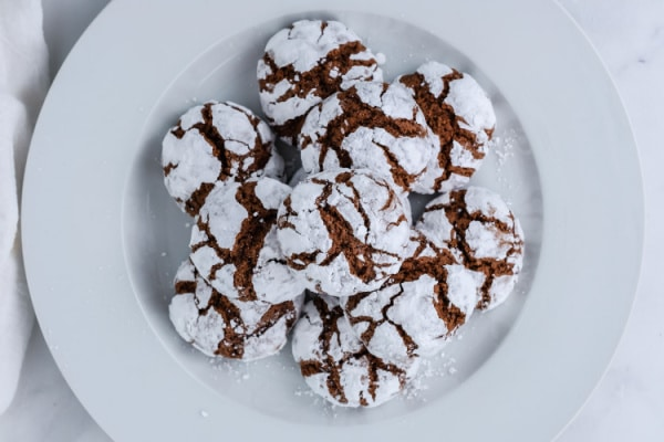 a white plate full of chocolate crinkle cookies
