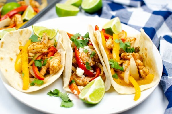 three shrimp fajitas with peppers and onions