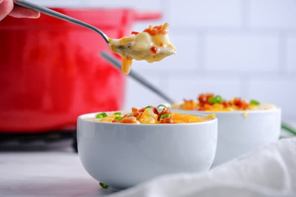 a white bowl with potato soup and a spoon with soup on it