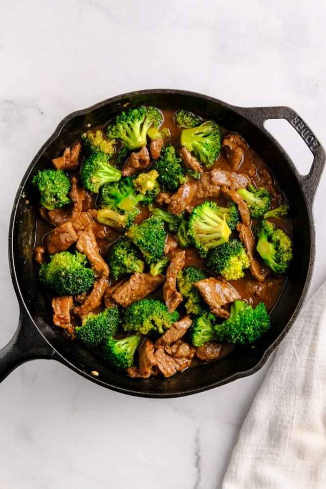 beef and broccoli in a cast iron pan