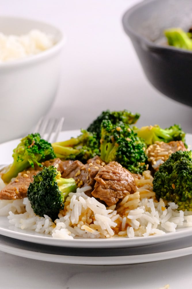 a white plate with beef and broccoli over white rice
