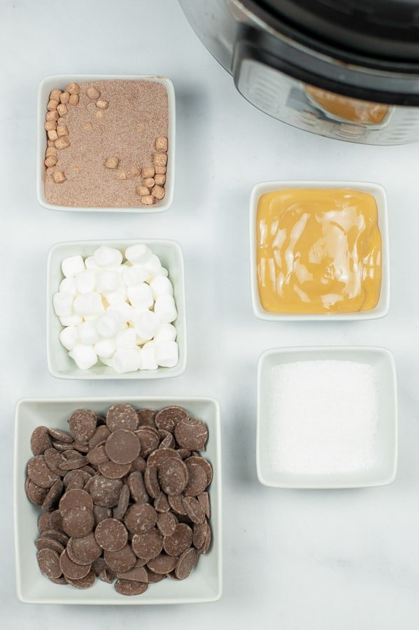 several white bowls with chocolate, mini marshmallows, cocoa powder, caramel, and salt