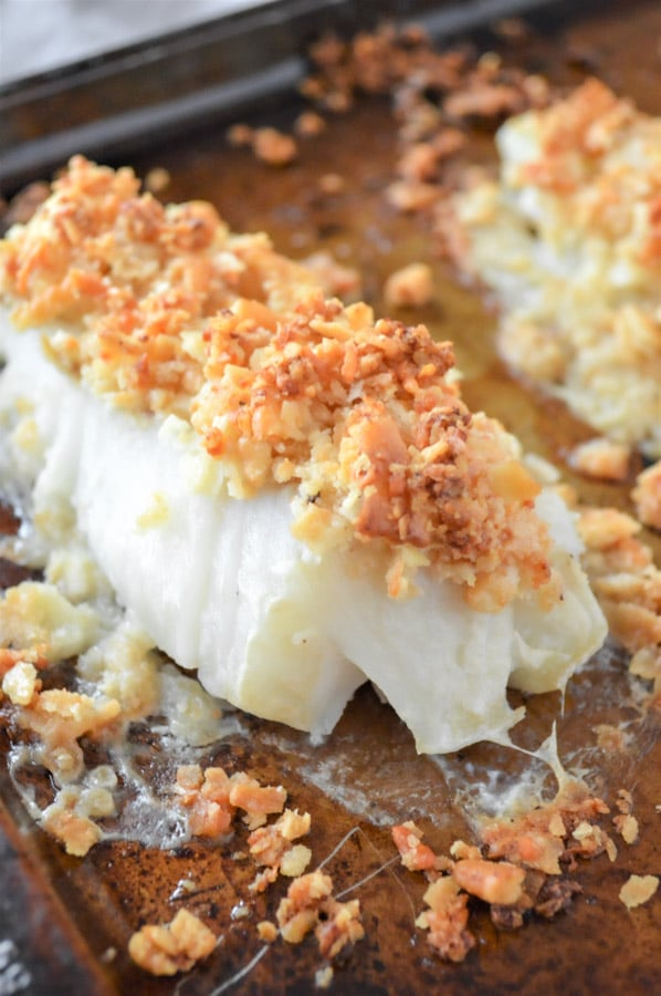 cod fillet on a baking sheet with a crispy breadcrumb topping