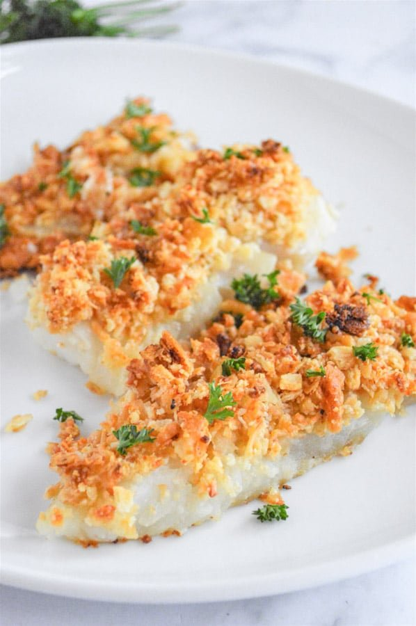a white plate with three oven baked cod fillets topped with a crispy topping