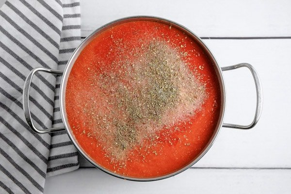 pot with marinara sauce topped with dried basile