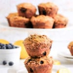 two lemon blueberry muffins stacked with a stand full of muffins in the background