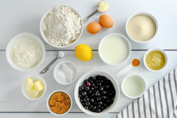ingredients for lemon blueberry muffins in small bowls and measuring spoons