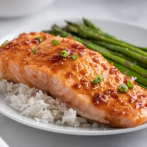 salmon fillet with maple soy glaze on a bed of white rice with asparagus on the side