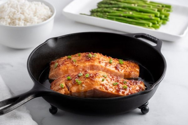 two salmon fillets in a cast iron pan with a bowl of white rice and a plate of asparagus in the background