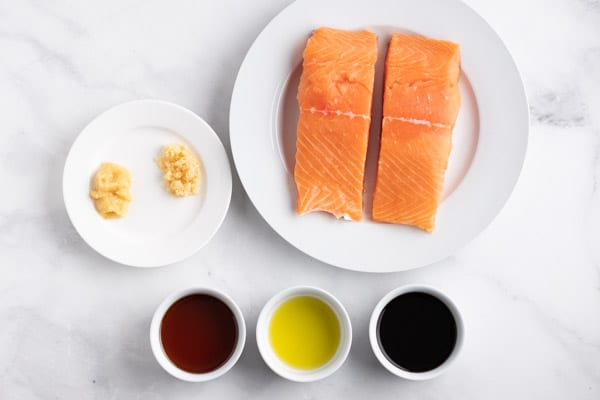 raw salmon on a plate with bowls of soy, maple syrup, and oil