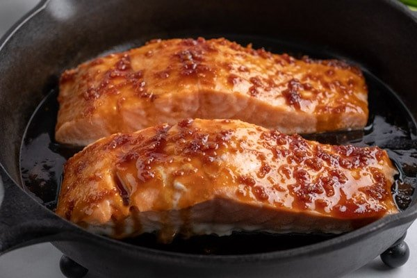 two salmon fillets in a cast iron pan topped with maple soy sauce