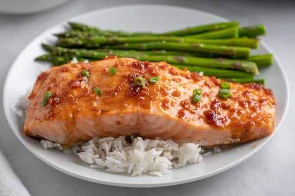 a white plate with a salmon fillet over white rice and a side of asparagus