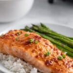 salmon fillet topped with chives and soy maple glaze on a plate with rice and asparagus