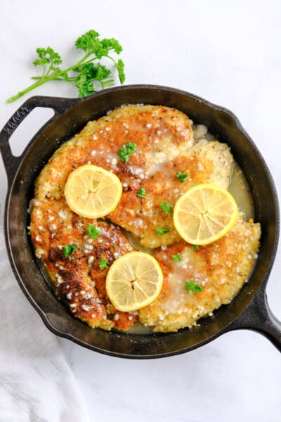 four breaded chicken breasts in a cast iron skillet with lemon slices