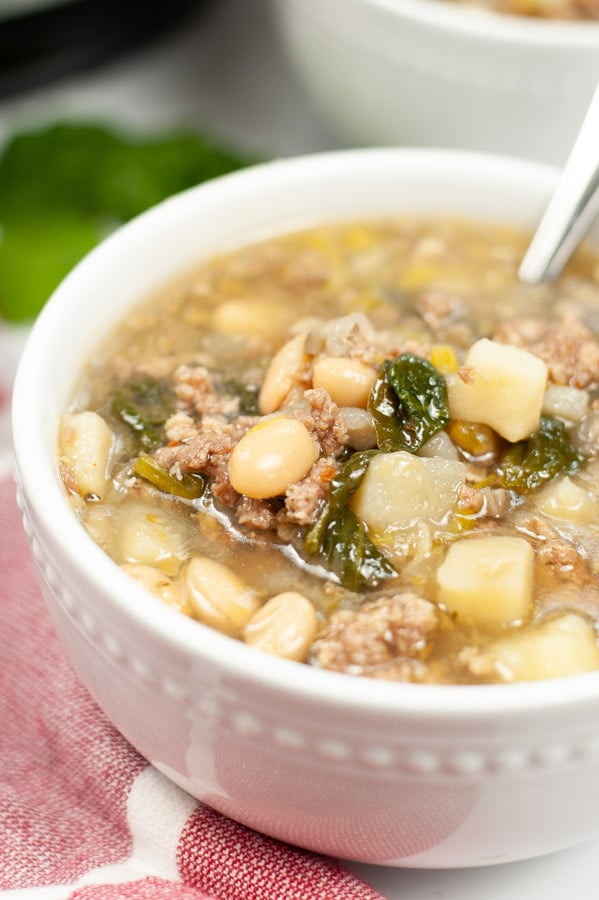 closeup of white bean sausage spinach soup in a white bowl