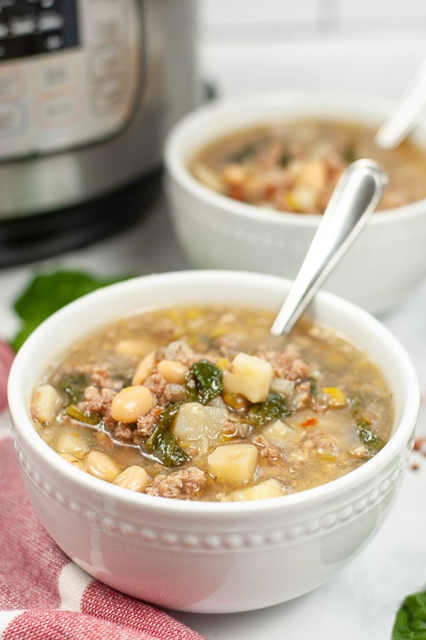 sausage potato spinach soup in a white bowl with a spoon