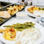 chicken with creamy sauce with diced potatoes and greens beans on a white plate