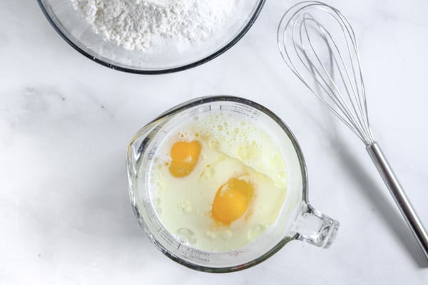 two eggs in a measuring cup with milk