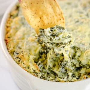 spinach artichoke dip being scooped out of a dish