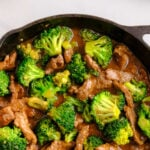 a cast iron skillet with beef strips and broccoli covered in a brown sauce