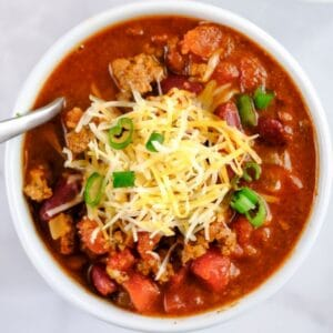 closeup of bowl of classic chili topped with cheese and green onion slices
