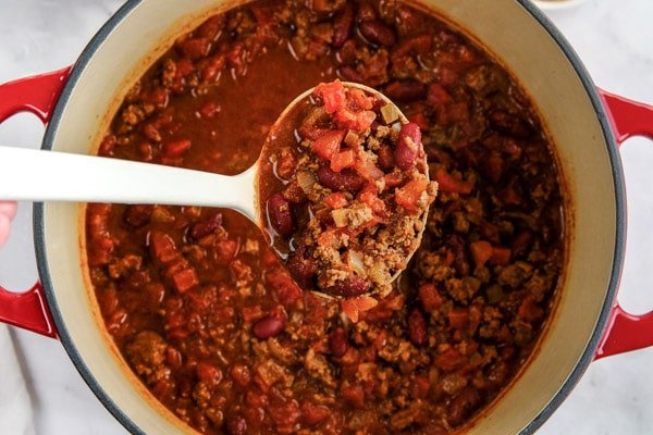a big spoonful of chili over a pot full