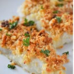 baked cod topped with crispy cracker topping on a white plate