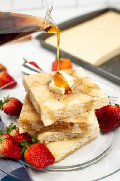 syrup being poured over a stack of sheet pan pancakes with strawberries on the plate
