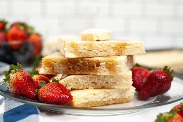 a stack of sheet pan pancakes on a glass plate with strawberries