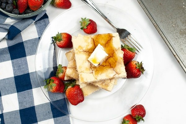 one pan pancakes on a glass plate with strawberries with a blue and white checker napkin
