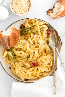 closeup of fettuccine noodles with asparagus and bacon with a spoon and bread