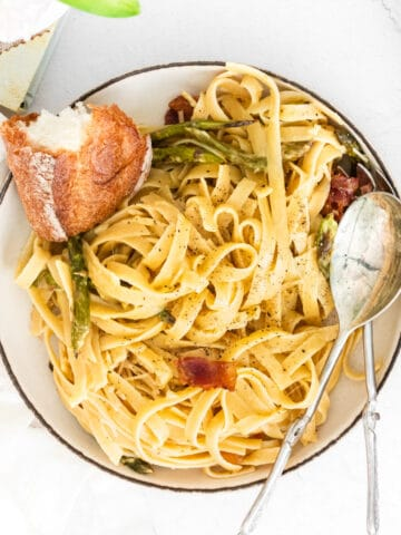 closeup of fettuccine with asparagus and bacon in a bowl with bread and spoon