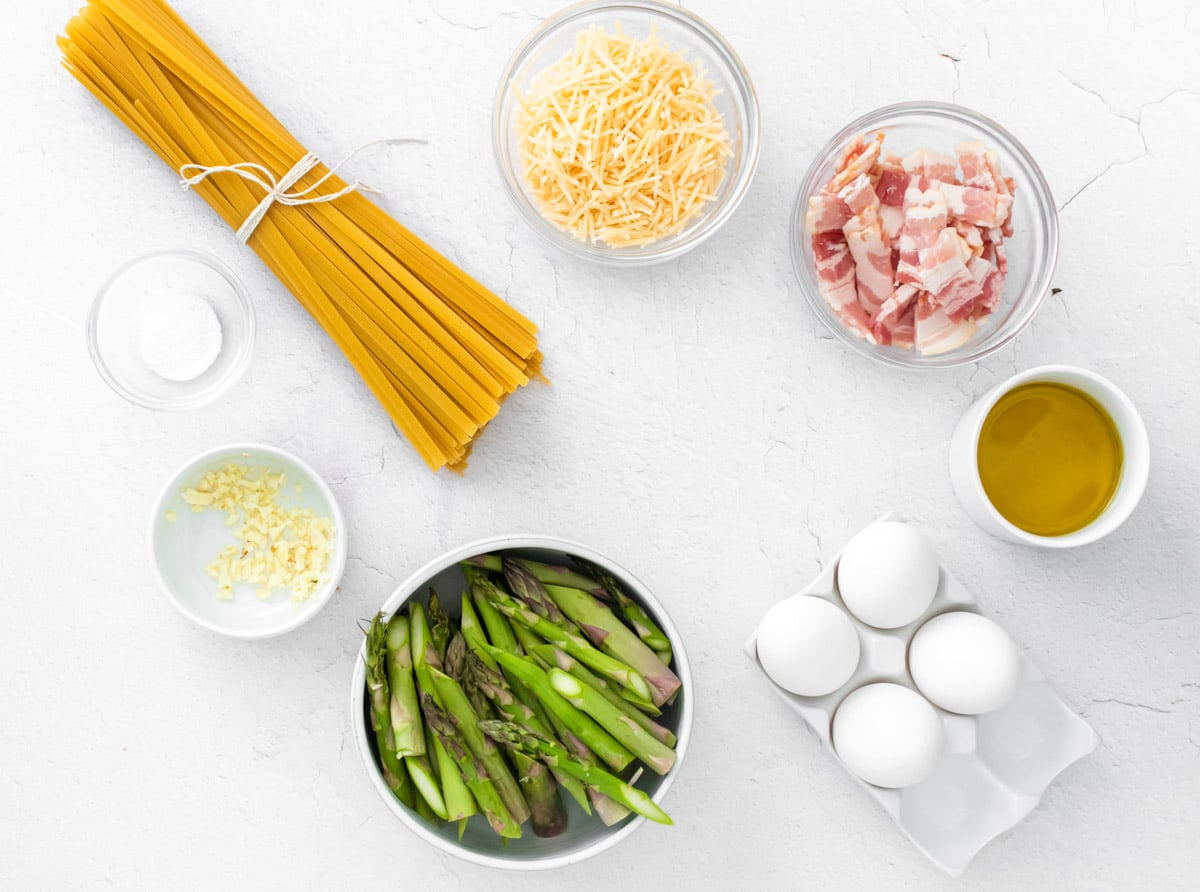 dry fettuccine noodles and bowls with asparagus bacon eggs and oil