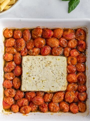 square white baking dish with feta cheese block, italian seasoning and cooked cherry tomatoes