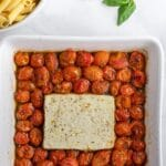 a white baking dish with cooked cherry tomatoes with a block of feta cheese in the center