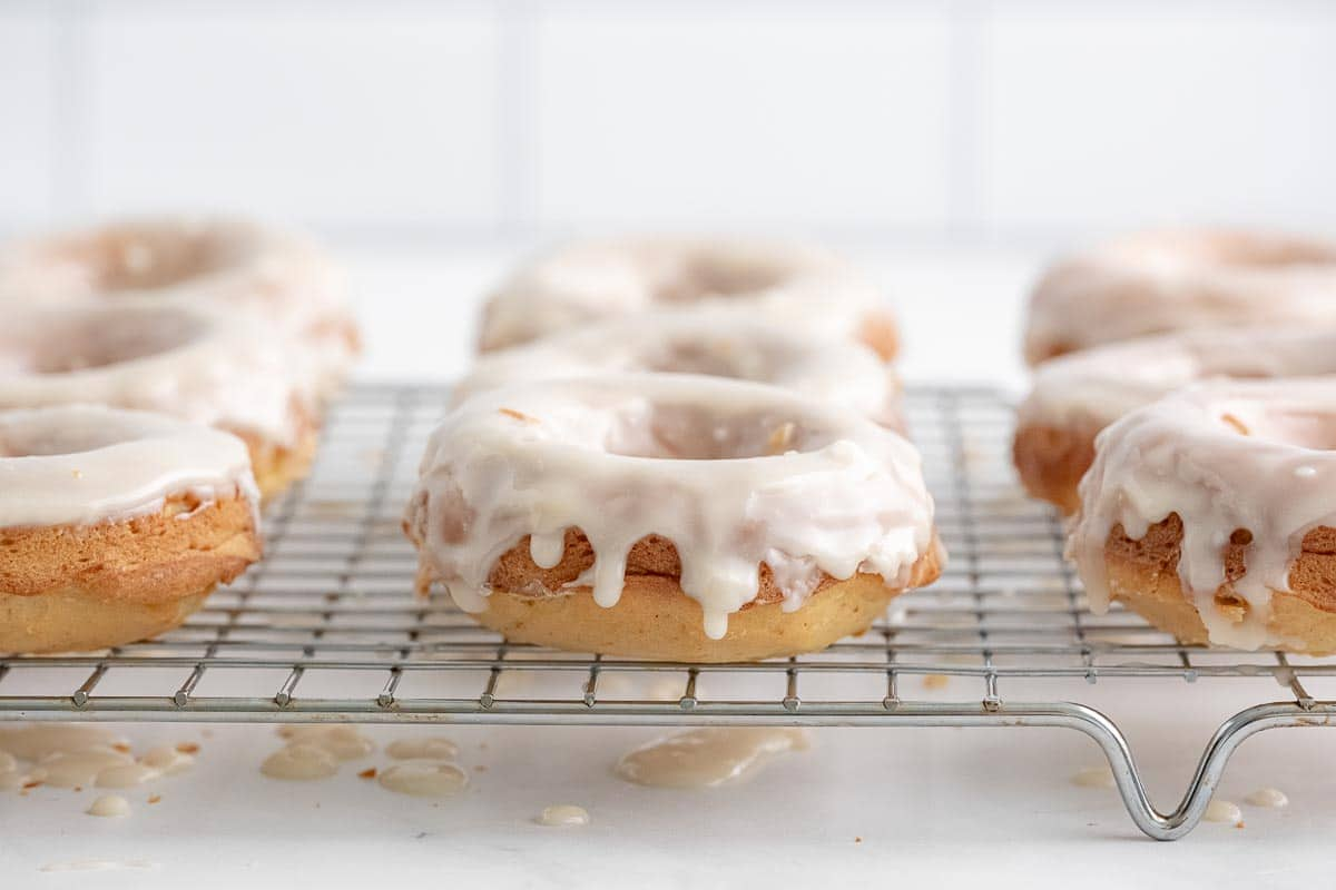 several glazed donuts on a wire rack