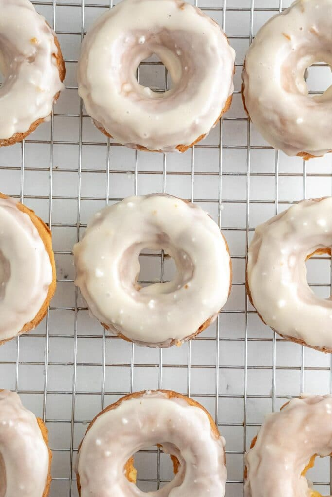 several glazed donuts on a silver wire rack