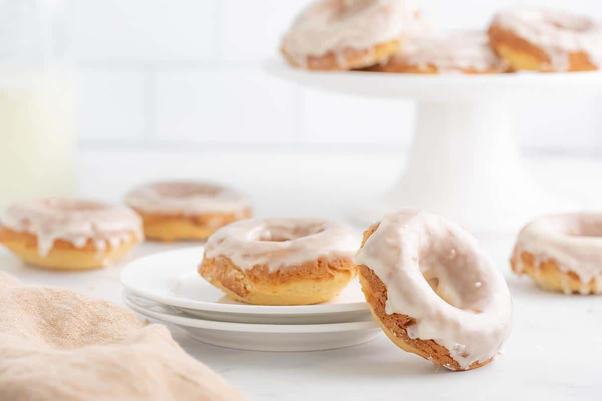 a white plate with a glazed donut with another donut leaning on the plate and a stand full of donuts in the background