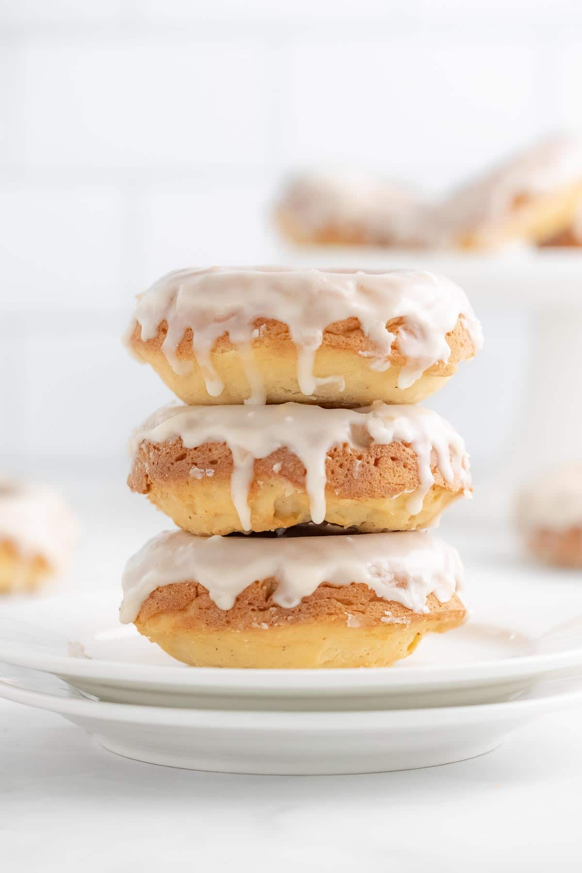 a stack of three glazed donuts on a white plate
