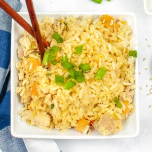 overhead of chicken fried rice in a white bowl with chop sticks