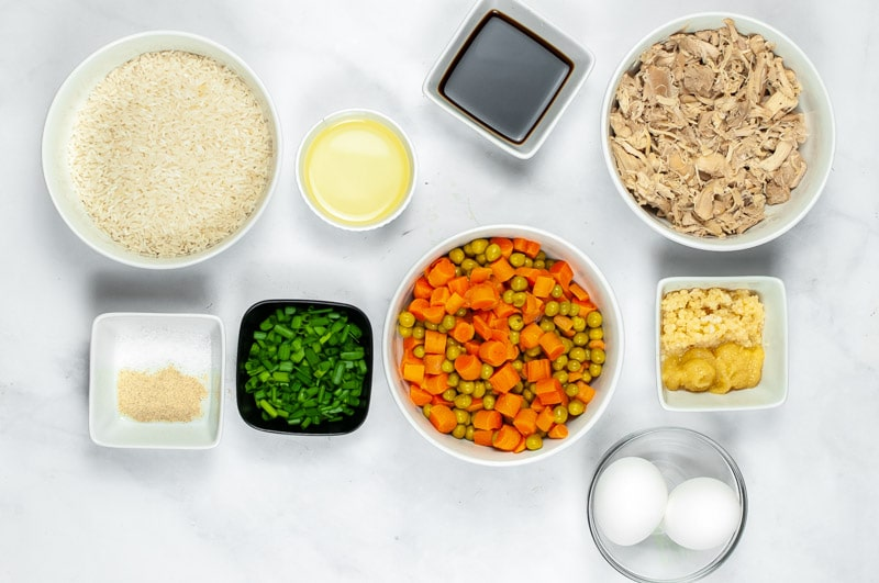 several white bowls with shredded chicken, rice, peas and carrots, eggs, green onions, ginger and garlic