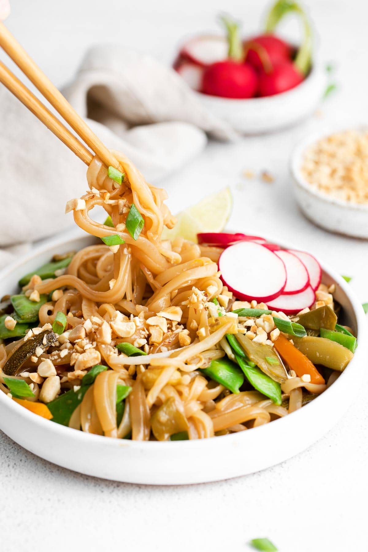 rice noodles with fresh radishes and crushed peanuts being twirled by chopsticks