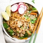 closeup of vegetarian pad thai with rice noodles, crushed peanuts and slices of radish