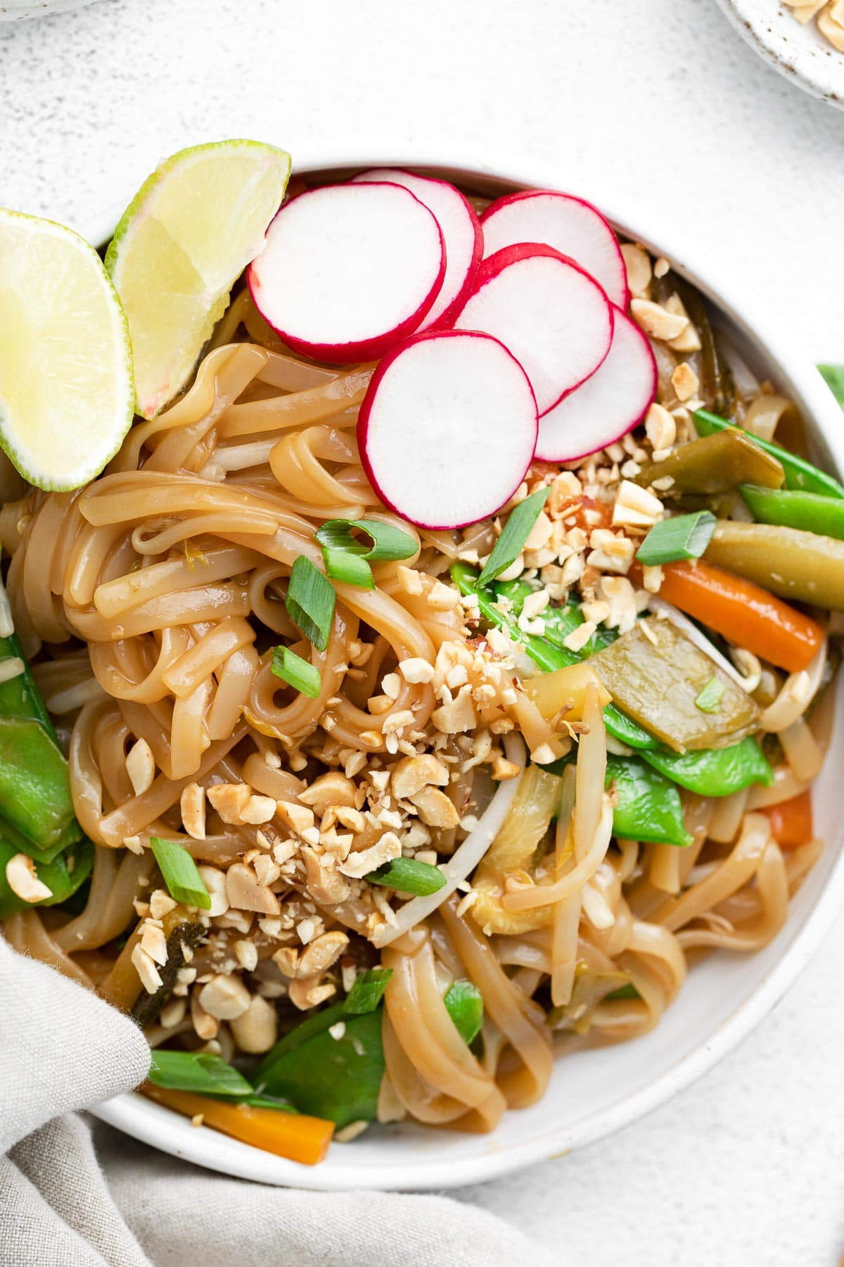 a large white bowl of rice noodles, fresh radishes, scallions, and crushed peanuts