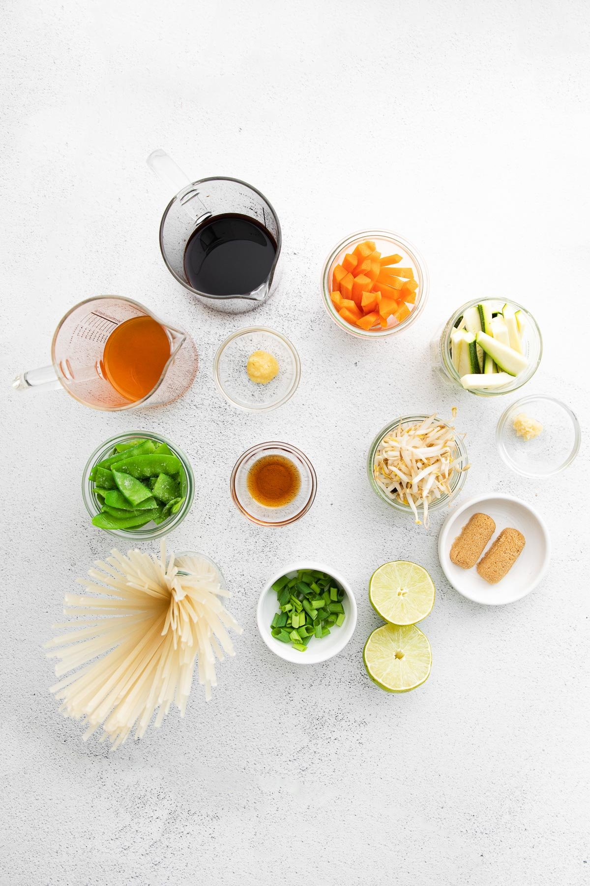several glass bowls filled with ingredients for vegetable pad thai